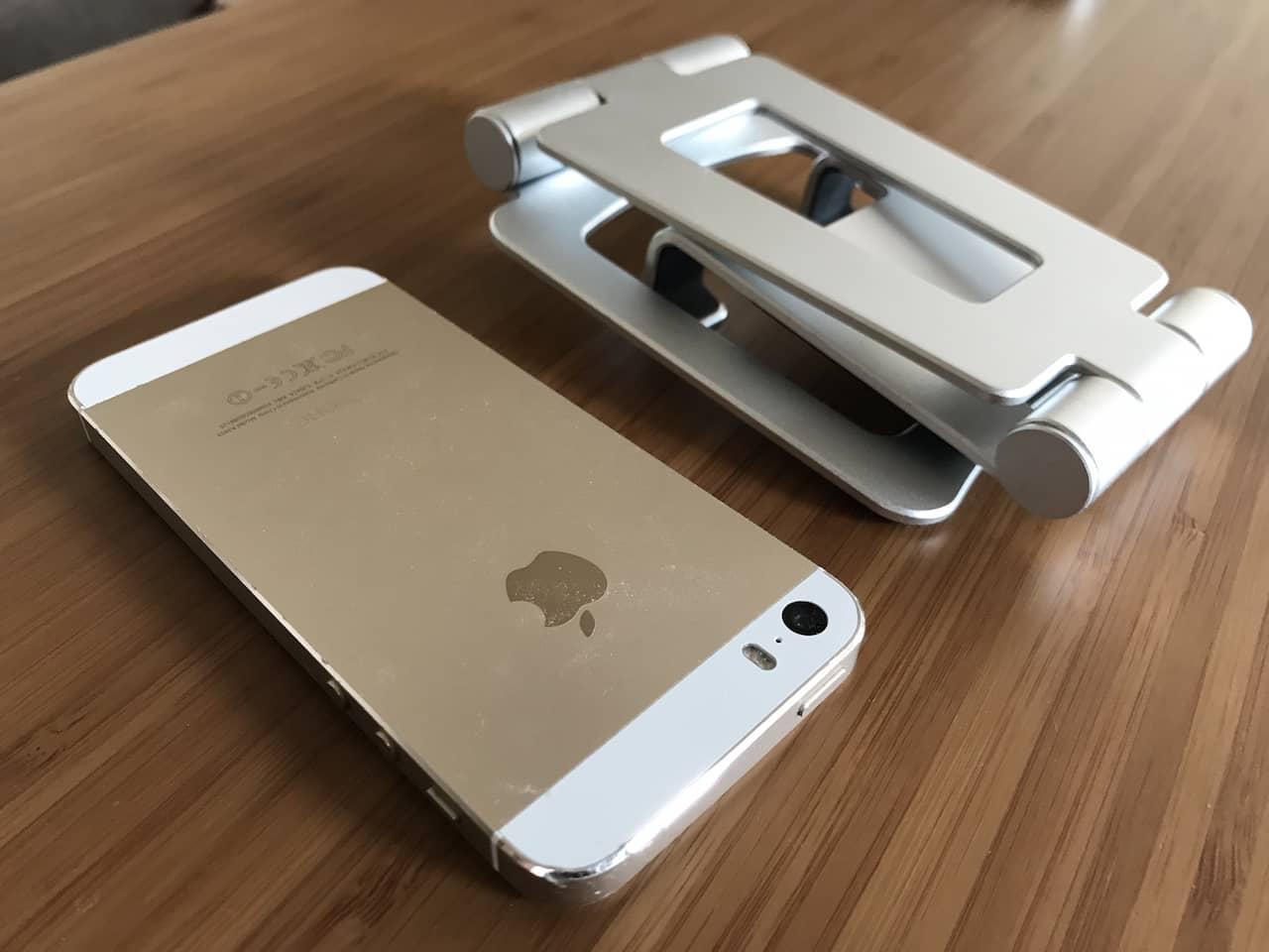 iPhone 5sと同じくらいの大きさに折り畳まれたシルバーのタブレットスタンドです。