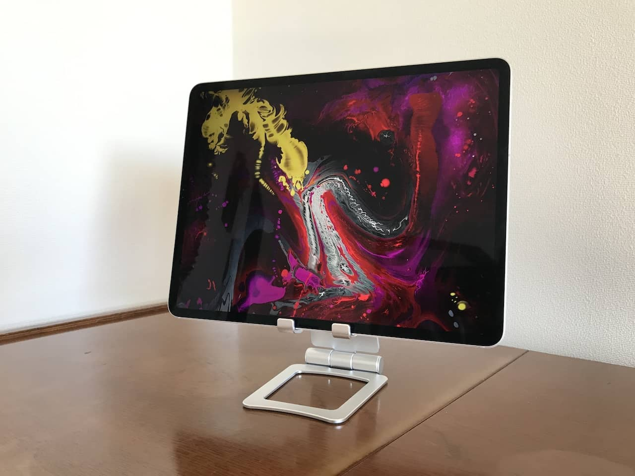 シルバーのタブレットスタンドに幾何学模様の画像を表示したiPad 12.9インチがのっています。
