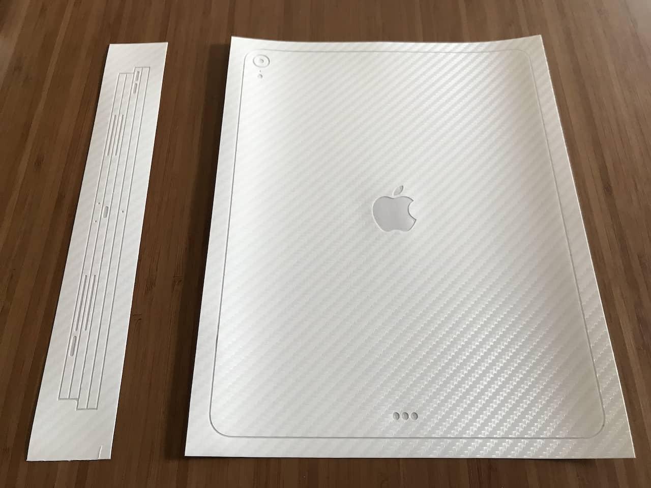ipad用のホワイトのカーボン柄のスキンシールが木目調のテーブルの上に置いてあります。