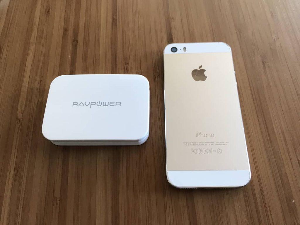 充電器とiPhone 5sが木製のデスクの上に置かれています