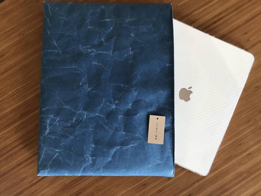 木製テーブルの上に青いsiwaのケースと白いipad proが置かれています