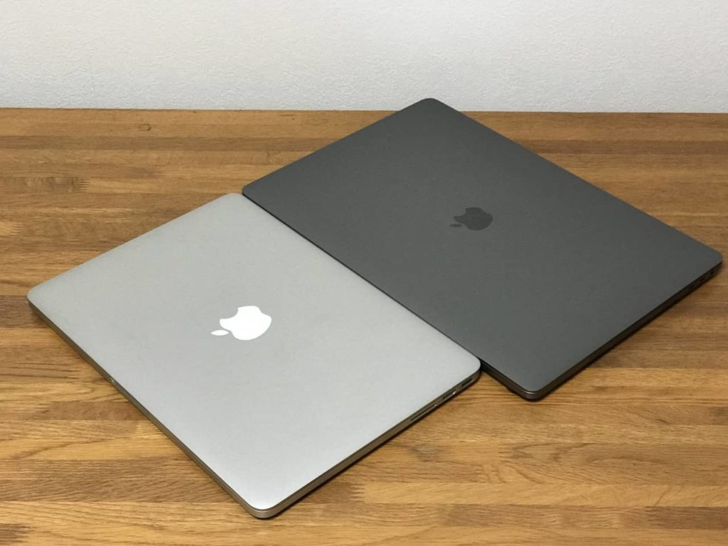 Macbook Pro 13インチと16インチが木製デスクの上に置かれています